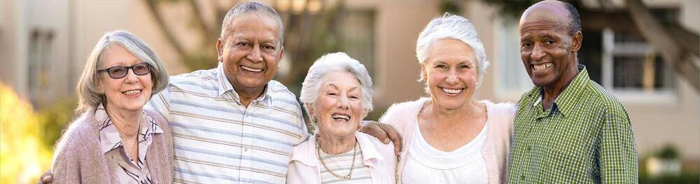 A group of older men and women smile for a photograph outside of their housing units.
