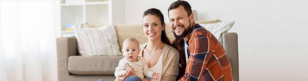 Husband, wife, and child sitting on the floor in front of their couch.